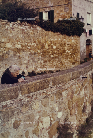 CGD-F-000820-0000 - An old woman observes the landscape from a small wall of a country in the Tuscan countryside - Date of photography: 09/1973 - Fratelli Alinari Museum Collections-Corinaldi Donation, Florence
