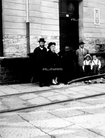 CRA-F-000005-0000 - Portrait of a group of emigrants, including the Hassid rabbi, waiting near a house turned into temporary lodgings in Trieste - Date of photography: 1923 ca. - Alinari Archives-Camerini archive, Florence