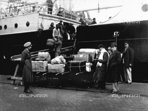 CRA-F-000011-0000 - An officer of the maritime terminal of Trieste is controlling the work of the porters loading the baggage of the emigrants on the ship 'Marta Washington'. On the right a few men are waiting to embark - Date of photography: 1923 ca. - Alinari Archives-Camerini archive, Florence
