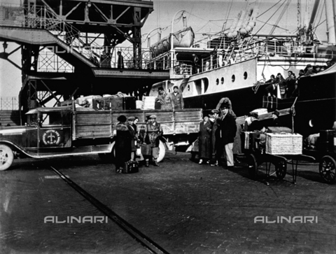 CRA-F-000015-0000 - The 'dock' of the harbor of Trieste. In the foreground a few porters are moving the luggage of the emigrants from a truck of the coooperative of municipal porter transporters to the ship 'Galilea' - Date of photography: 1923 ca. - Alinari Archives-Camerini archive, Florence