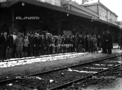 CRA-F-000025-0000 - Portrait of a large group of emigrants on the 'dock' of the central station of Trieste. Two employees of the railway police are watching - Date of photography: 1922-1930 ca. - Alinari Archives-Camerini archive, Florence