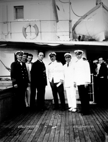 CRA-F-000030-0000 - Portrait of officers of the ship 'Carniolia' and the representatives of the 'Trieste Committee of assistance'. At the center of the group is the commander. In the background on the right the emigrants are waiting to leave - Date of photography: 1930 - Alinari Archives-Camerini archive, Florence