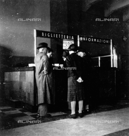 CRA-F-000038-0000 - Interior of the maritime station: in front of the ticket office a group of persons is seeing to the bureaucratic formalities before departure - Date of photography: 1930 ca. - Alinari Archives-Camerini archive, Florence