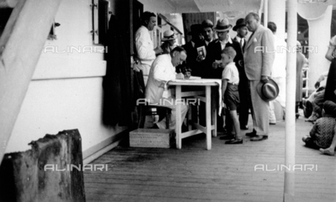 CRA-F-000070-0000 - Group of emigrants near a table where a merchant Marine soldier is registering the boarding - Date of photography: 1922-1930 - Alinari Archives-Camerini archive, Florence