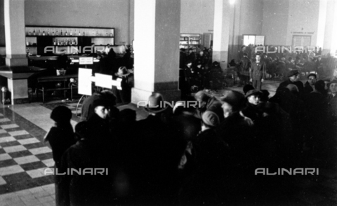 CRA-F-000076-0000 - The waiting room in the maritime station of Trieste where a large group of emigrants is waiting to embark on the ship. In the background the coffee bar - Date of photography: 1930 ca. - Alinari Archives-Camerini archive, Florence