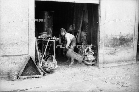 DAA-S-085004-0051 - Florence flood of November 4, 1966: a girl cleans a flooded antique shop - Data dello scatto: 06/11/1966 - Dufoto / Alinari Archives