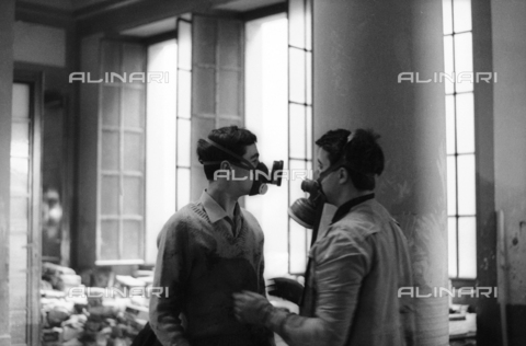 DAA-S-085671-0015 - Alluvione di Firenze del 4 novembre 1966: volontari con maschere durante il recupero dei libri alluvionati della Biblioteca Nazionale - Data dello scatto: 06-08/11/1966 - Dufoto / Archivi Alinari