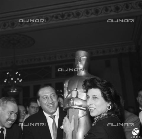 """DAD-S-000092-0010 - Anna Magnani abbraccia una statua riproducente il Premio Oscar, durante i festeggiamenti per la vincita del premio come interprete del film """"La rosa tatuata"""" - Data dello scatto: 1955 - Istituto Luce/Gestione Archivi Alinari, Firenze"""