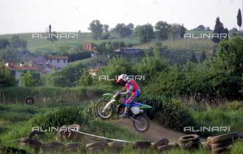 DAL-F-004451-0000 - A motorcyclist jumping over a bump on a motocross track. Environs of Castelnuovo d'Elsa, Castelfiorentino, Florence