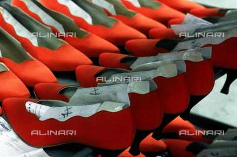 DAL-F-004716-0000 - Fila di scarpe rosse coi tacchi alti da donna appena realizzate all'interno di una fabbrica di calzature. Montelupo Fiorentino, Firenze. - Data dello scatto: 1992 - Archivi Alinari, Firenze