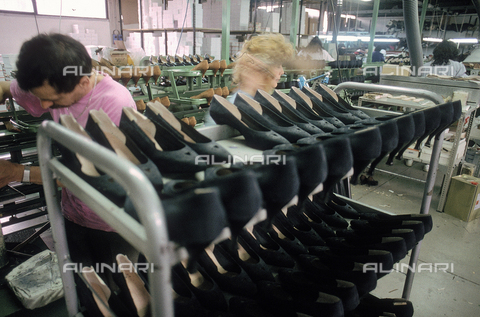DAL-F-004742-0000 - Interno di un calzaturificio con degli operai che sistemano delle scarpe da donna su degli scaffali metallici. Montelupo Fiorentino. - Data dello scatto: 1992 - Archivi Alinari, Firenze
