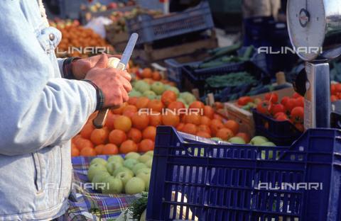 DAL-F-004842-0000 - Arance e mele esibite in un banco ambulante durante il mercato. In primo piano le mani di un uomo che taglia un frutto. Anselmo, frazione di Montespertoli. - Data dello scatto: 11/03/1992 - Archivi Alinari, Firenze