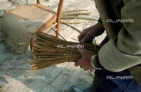 DAL-F-005179-0000 - Primo piano di un uomo che maneggia un fascio di vimini. Montegufoni, Montespertoli. - Data dello scatto: 11/03/1992 - Archivi Alinari, Firenze