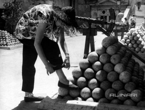DPA-F-000545-0000 - Una donna si aggiusta l'orlo dei pantaloni, tenendo la gamba poggiata su un mucchio di palle di cannone all'interno di Castel Sant'Angelo, a Roma. - Data dello scatto: 1960 ca. - Archivi Alinari, Firenze