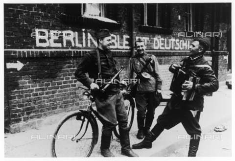 "EVA-S-001014-3558 - Soviet soldiers with an accordion on a street in Berlin. Behind them, the words ""Berlin remains German"" (one of Goebbels' latest propaganda) - Data dello scatto: 1945 - ALEXA / © Mary Evans / Alinari Archives"