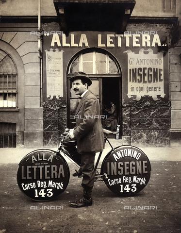 FBC-F-002323-0000 - Un uomo in bicicletta fa pubblicità al negozio di insegne che si trova alle sue spalle - Data dello scatto: 1915 ca. - Archivi Alinari, Firenze