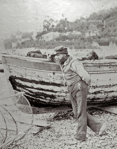 FBQ-F-001963-0000 - Portrait of a fisherman in work clothes. He is posing leaning against a boat and observing the horizon. On the ground a circular net - Data dello scatto: 1870 -1880 - Archivi Alinari, Firenze