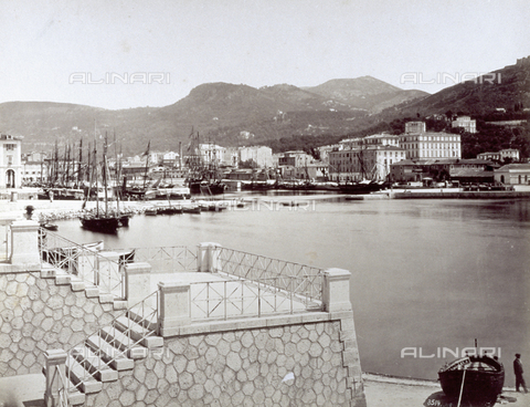 FBQ-F-003451-0000 - The port of Nice with numerous sailboats, in the foreground, on the right, a boat drawn up on the beach. On the left a terrace. In the background, the hills which surround the city - Data dello scatto: 1880 ca. - Archivi Alinari, Firenze