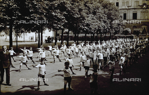 FBQ-F-004146-0000 - A group of young fencers shown practicing outside. In the background rows of trees and buildings