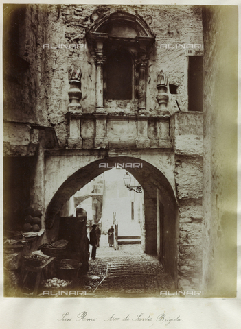 FBQ-S-003242-0002 - A lane in old San Remo. In the foreground the Arch of Santa Brigida, consisting of an arch with a wall on top decorated with two sculptured torches and an aedicule shaped window. Beneath the arch are baskets full of farm produce. Along the road, with its typical cobblestones, are three local figures - Data dello scatto: 1890- 1895 ca- - Archivi Alinari, Firenze