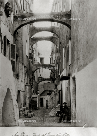 FBQ-S-003242-0005 - Vicolo del Gioco della Palla in San Remo. A child and an elderly woman are seated in front of the doorway of their homes along this brief stretch of road. There are numerous arches between the buildings which cross the road. At the top, two women are looking out of a window - Data dello scatto: 1890 -1895 ca. - Archivi Alinari, Firenze