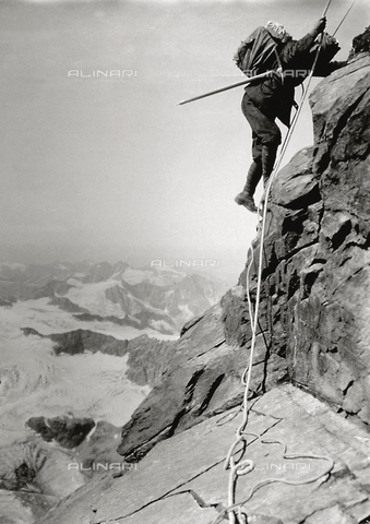 FBQ-S-004232-0003 - Alpinist in a roped party on a rock wall. In the background mountain landscape with glacier
