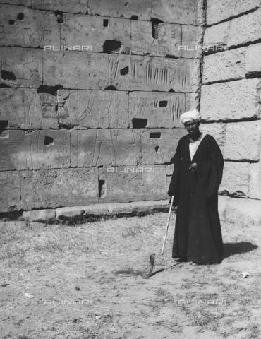 FCA-F-000150-0000 - Un uomo ritratto vicino a una parete incisa con figure di divinità, Egitto - Data dello scatto: 1950-1960 - Archivi Alinari, Firenze
