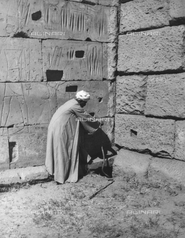 FCA-F-000157-0000 - Un uomo ritratto vicino a una parete incisa con figure di divinità, Egitto - Data dello scatto: 1950-1960 - Archivi Alinari, Firenze