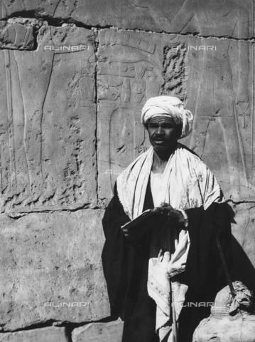 FCA-F-000159-0000 - Un uomo ritratto vicino a una parete incisa con figure di divinità, Egitto - Data dello scatto: 1950-1960 - Archivi Alinari, Firenze