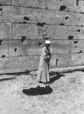 FCA-F-000160-0000 - Un uomo ritratto vicino a una parete incisa con figure di divinità, Egitto - Data dello scatto: 1950-1960 - Archivi Alinari, Firenze