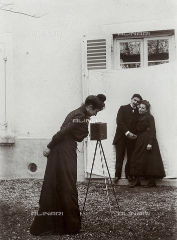 FCC-F-010282-0000 - Fotografa che guarda l'inquadratura, mentre ritrae una giovane coppia. - Data dello scatto: 1902 - Archivi Alinari, Firenze
