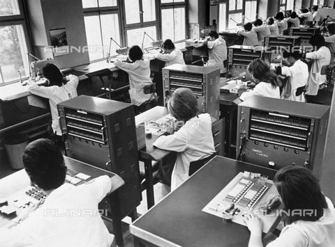 FCC-F-022968-0000 - Operaie intente alla costruzione di un apparato elettronico chiamato Omega-Metric creato appositamente per effettuare una particolare e delicata operazione dell'orologio, per quanto riguarda il meccanismo del bilanciere - Data dello scatto: 1960 ca. - Archivi Alinari, Firenze
