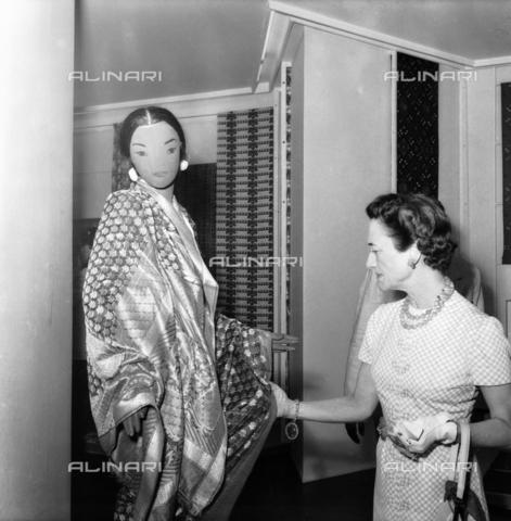 FVA-S-208000-0009 - Princess Alice, Duchess of Gloucester, examines a fabric during her visit to C.I.A.C. (International Center for Art and Costume), Palazzo Grassi, Venice - Data dello scatto: 1955 ca. - Archivi Alinari, Firenze