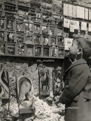 """FVD-F-014369-0000 - """"San Giminiano con Alessandro"""", ritratto di bambino mentre osserva l'espositore di cartoline"""