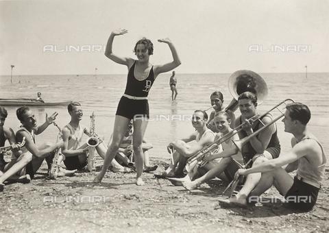 FVQ-F-008886-0000 - Una giovane donna, circondata da alcuni musicisti, balla su una spiaggia del Lido di Venezia - Data dello scatto: 1920 ca. - Archivi Alinari, Firenze