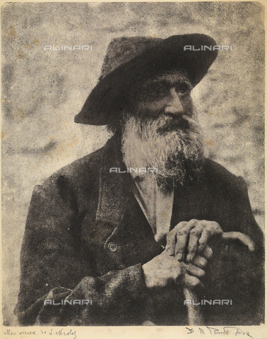 FVQ-F-035010-0000 - Half-length potrait of an elderly man with a thick unruly beard, wearing a dark jacket and hat. He looks sad and is resting his gnarled hands on a stick. The photograph is particularly artistic in the pictorial effects of the image and the background which seem to merge in a dense atmosphere - Date of photography: 1925 - 1935 ca. - Fratelli Alinari Museum Collections, Florence