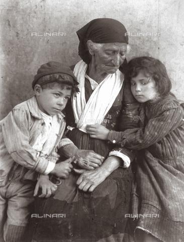 FVQ-F-040096-0000 - Portrait of an elder Sicilian woman and two children in poor clothes - Data dello scatto: 1898 - Archivi Alinari, Firenze