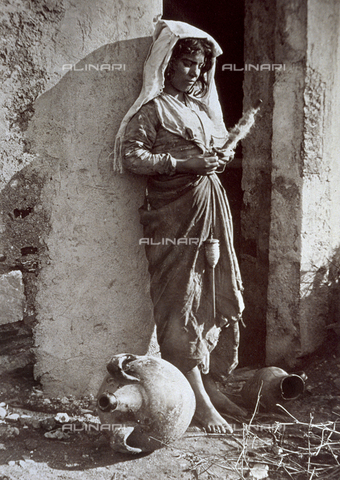 FVQ-F-044112-0000 - Full-length portrait of a native child in traditional costume. The young girl, leaning against the wall of a dilapidated building, appears to be engrossed in the act of winding wool. An amphora is lying on the ground in the forefront - Data dello scatto: 1895 - 1905 ca. - Archivi Alinari, Firenze