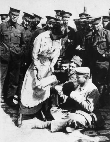 FVQ-F-068616-0000 - L'immagine mostra una donna francese che soccorre alcuni prigionieri tedeschi feriti, seduti per terra. - Data dello scatto: 1914 - 1917 - Archivi Alinari, Firenze