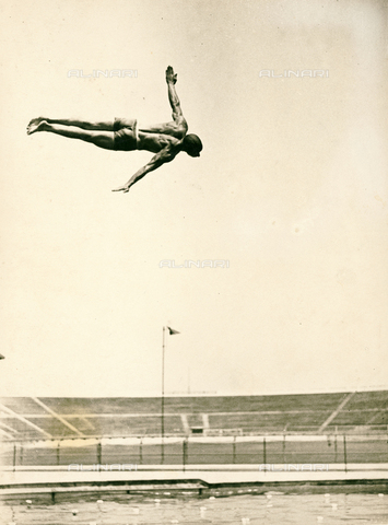 FVQ-F-119109-0000 - The image shows a young man portrayed while taking an acrobatic dive; in the background, an athletical stadium.
