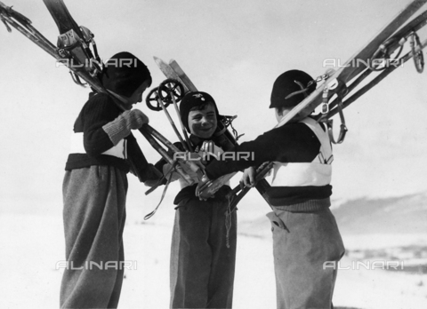 """FVQ-F-119142-0000 - Children """"Figli della Lupa"""" (Son of the She Wolf) are happy on the snow fields. Three of them are talking with each other, with the skis on their shoulders."""