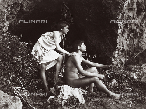 FVQ-F-138589-0000 - Artistica photograph invoking the Arcadian atmosphere of the ancient Greece. An adolescent nude in profile, is sitting in front of a grotto. Behind the youth is a boy dressed as a shepherd - Data dello scatto: 1900 - 1909 ca. - Archivi Alinari, Firenze