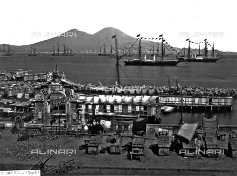 "FVQ-F-141008-0000 - ""S.Lucia. Naples"". The Gulf of Naples photographed from Via Partenope. In the foreground the Fountain of the Immacolatella and a few stands. In the background smoking Mount Vesuvious. Numerous ships are lying at anchor near the Port of Santa Lucia - Data dello scatto: 1865 ca. - Archivi Alinari, Firenze"