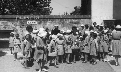 FVQ-F-154659-0000 - Gruppo di bambine in abbigliamento scolastico. Sul muro sono visibili scritte fasciste - Data dello scatto: 1920 - 1930 ca. - Archivi Alinari, Firenze