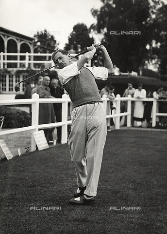 FVQ-F-193362-0000 - The captain F. Francis takes a shot at a golf tournament; in the background, spectators
