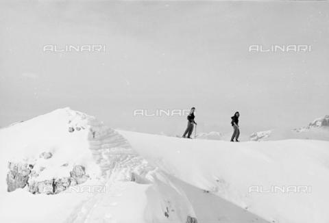 GBA-S-000178-005A - Veduta di montagna innevata con donne sugli sci, Cortina d'Ampezzo - Data dello scatto: 06/02-27/02/1941 - Archivi Alinari, Firenze