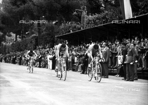 GCQ-A-003401-0047 - Cyclists during a competition. At the edge of the road and in the stands, there are several spectators and men in uniforms