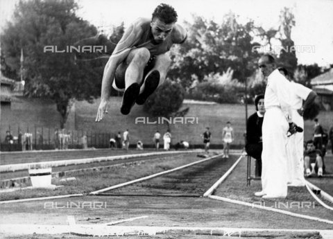 GCQ-A-003401-0059 - The ceremonies and games called by the Centro Sportivo Italiano: an athlete doing the long jump before the judges of the competition