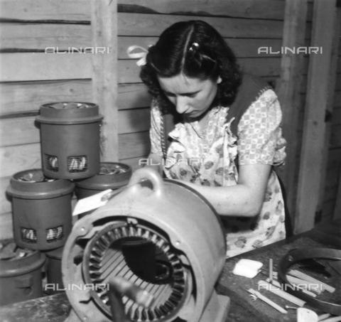 """GCQ-F-006989-0000 - L'operaia italiana Francesca Corsini emigrata in Svizzera fotografata vicino ad un macchianario. La donna lavora presso la ditta """"Brown Boveri & Cie. A.G."""" a Baden, in Argovia - Data dello scatto: 1940 - 1950 - Archivi Alinari, Firenze"""