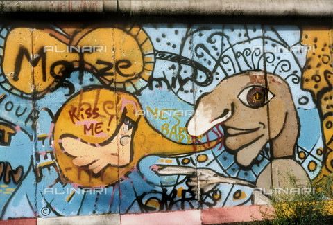 GRA-F-000011-0000 - Masculine face and comics, artwork by Thierry Noir and Christophe Bouchet. Graffiti & Wall Art on the Berlin Wall that fell down beginning from the night of 9th November 1989 - Data dello scatto: 1987 - Francesco and Alessandro Alacevich / Gremese Archive/Alinari Archives